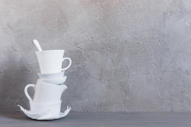 Weiße tonware auf dem tisch gegen die strukturierte graue wand