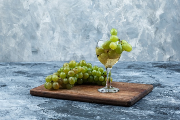 Weiße trauben der nahaufnahme, glas whisky auf schneidebrett auf dunklem und hellblauem marmorhintergrund. horizontal