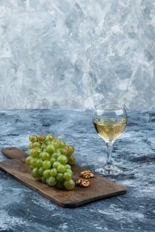 Weiße trauben der nahaufnahme, walnüsse auf schneidebrett mit glas whisky auf dunklem und hellblauem marmorhintergrund. vertikal