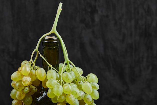 Weiße trauben und eine flasche wein auf dunkler oberfläche
