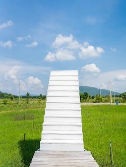 Weiße treppe vom grünen rasengarten bis zum wolkenhimmel, glaube und weg zum erfolgreichen konzept