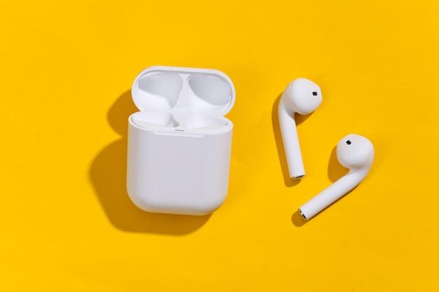 Weiße true-wireless-bluetooth-kopfhörer oder -ohrhörer mit ladehülle auf gelbem, hellem hintergrund.