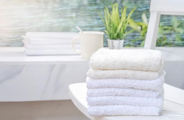 Weiße tücher auf weißem strandstuhl mit kopienraum auf unscharfem blauem seehintergrund
