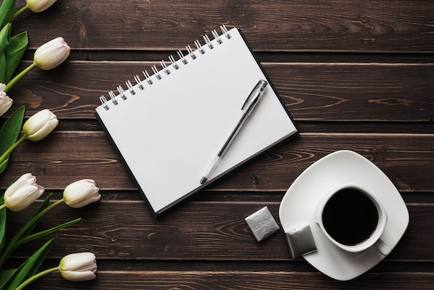 Weiße tulpen auf einem holztisch mit einem tasse kaffee und einem leeren notizbuch