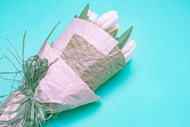 Weiße tulpen auf einer blauen tabelle. kopieren sie platz.