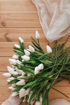 Weiße tulpen auf natürlichem hölzernem hintergrund topview. frühlingsmelodie