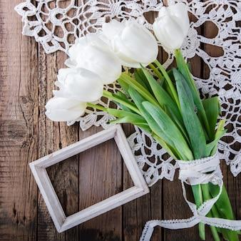 Weiße tulpen des blumenstraußes mit rahmen für foto oder text