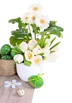 Weiße tulpen, gerberas und ostereier auf dem holz lokalisiert auf weiß