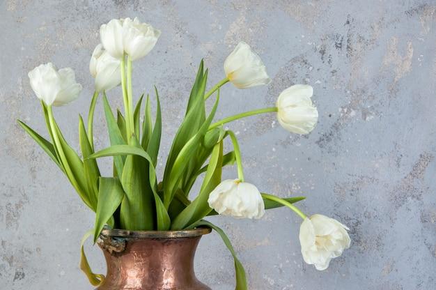 Weiße tulpen in alter kupfervase Premium Fotos