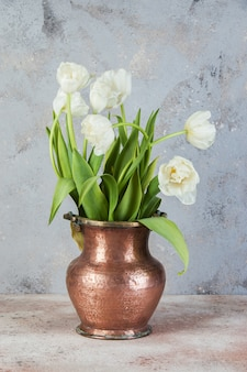 Weiße tulpen in alter kupfervase
