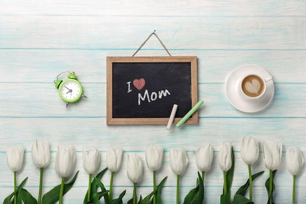 Weiße tulpen mit kreidebrett, tasse kaffee und wecker auf blauen hölzernen brettern. muttertag