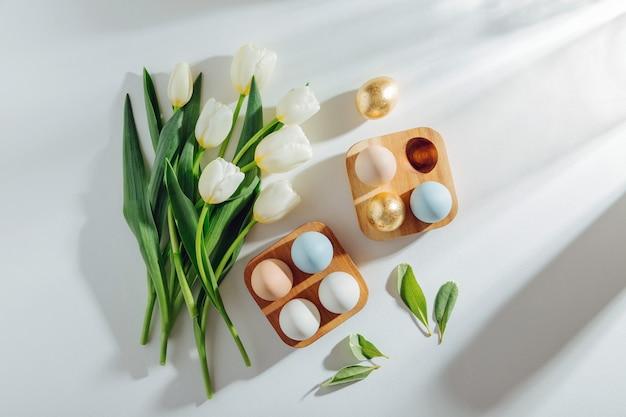 Weiße tulpen und eier im hölzernen eierkarton mit sonnenlicht auf weißem hintergrund. stilvolle frühlingskompositionen. ostern-konzept.