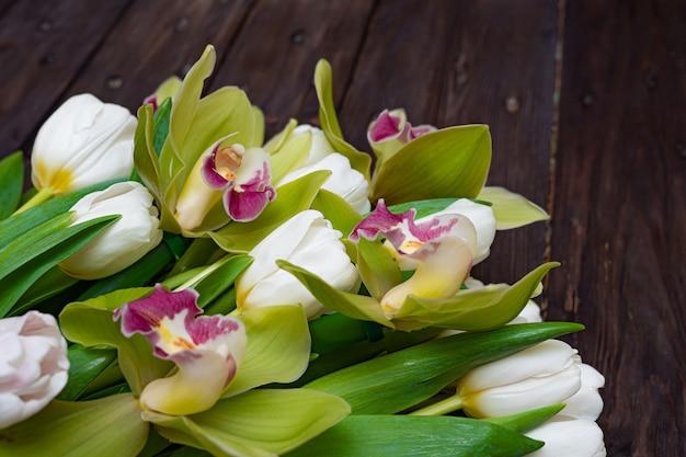 Weiße tulpen und grüne orchideen auf einem dunklen holztisch