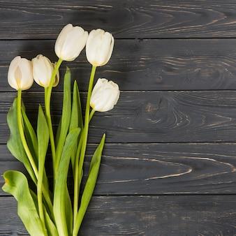 Weiße tulpenblumen auf dunklem holztisch