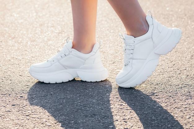 Weiße turnschuhe an den beinen des mädchens auf dem asphalt