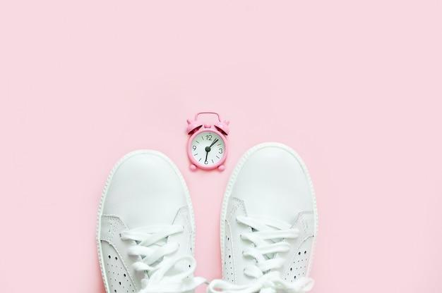 Weiße turnschuhe auf einem rosa hintergrund in einer rosa uhr