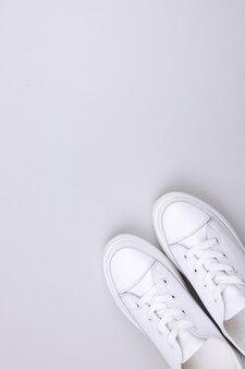 Weiße turnschuhe auf grauem hintergrund