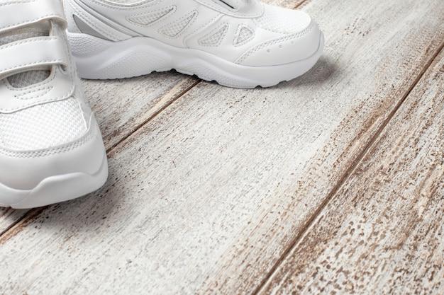 Weiße turnschuhe auf hellem hintergrund seitenansicht eines modischen kinderleder-stoffs...