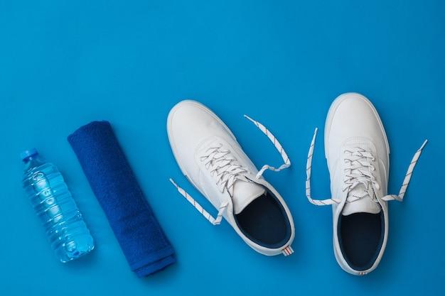 Weiße turnschuhe, eine flasche wasser und ein blaues handtuch auf blauem grund. sportlicher stil. flach liegen. der blick von oben.