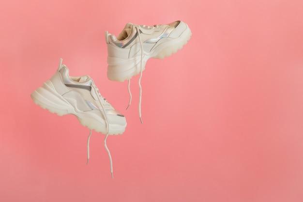 Weiße turnschuhe fliegen. weibliche weiße lederschuhe mit schnürsenkeln auf rosa hintergrund. paar stylische sneaker bequeme sportswear hipster damenschuhe. platz kopieren.