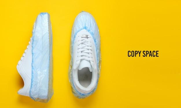 Weiße turnschuhe in stiefelabdeckungen auf gelbem grund. draufsicht. minimalismus. speicherplatz kopieren