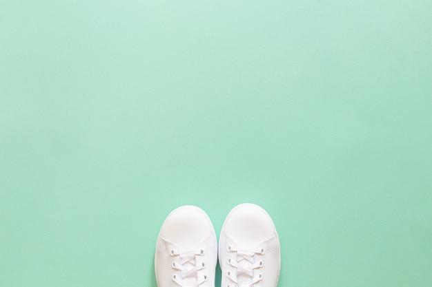 Weiße turnschuhe isoliert auf minzgrün