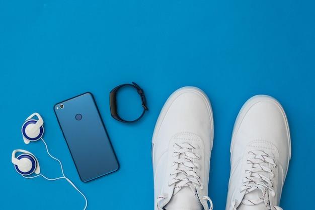 Weiße turnschuhe, kopfhörer, intelligentes armband und blaues smartphone auf blauem hintergrund. sportlicher stil. flach liegen. der blick von oben.