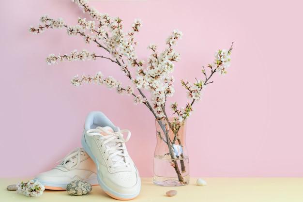 Weiße turnschuhe mit blumen auf rosa hintergrund vorderansicht paar neue schuhe