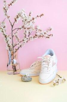 Weiße turnschuhe mit blumen auf rosa wand vorderansicht paar neue schuhe