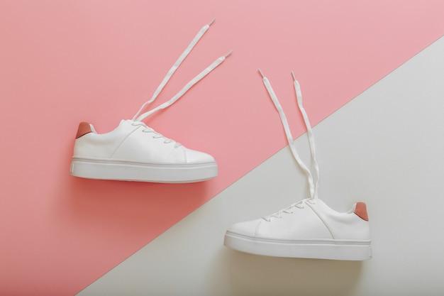 Weiße turnschuhe mit fliegenden schnürsenkeln. paar stylische sneaker bequeme sportswear hipster damenschuhe. weibliche weiße lederschuhe mit schnürsenkeln auf rosa hintergrund. ansicht von oben.