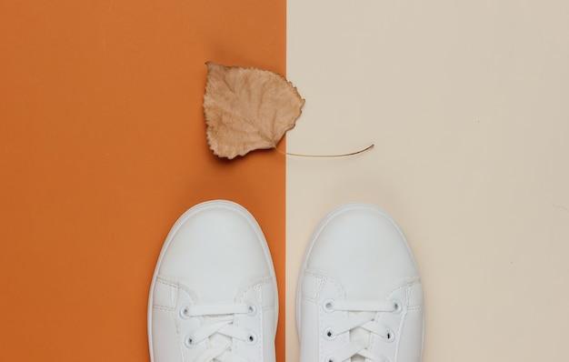Weiße turnschuhe mit trockenem herbstblatt auf farbigem papier