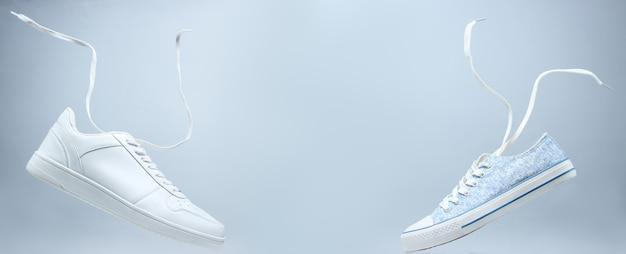 Weiße turnschuhe und schwebende schnürsenkel auf grau