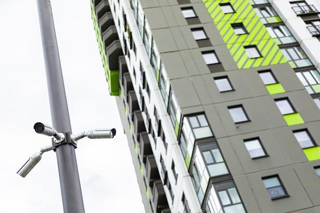 Weiße überwachungskameras, die auf stapel nahe hohem wohnblock hängen