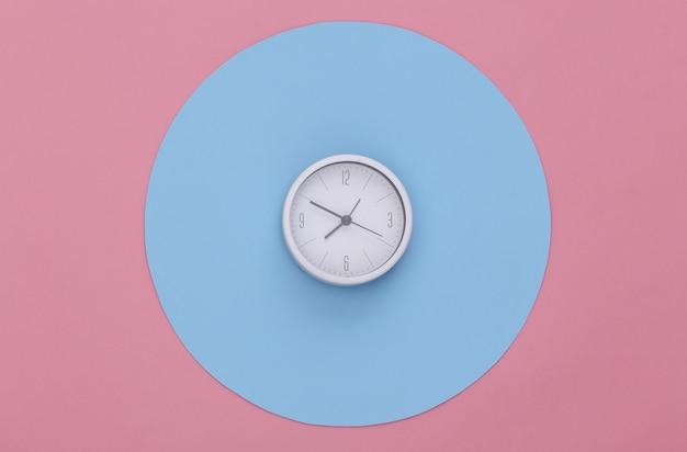 Weiße uhr auf rosa hintergrund mit blauem kreis. konzeptionelle studioaufnahme. minimalismus. ansicht von oben