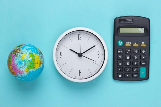 Weiße uhr mit einem globus, rechner auf blauer oberfläche. die zeit wird sich um den planeten kümmern. öko-thema. draufsicht