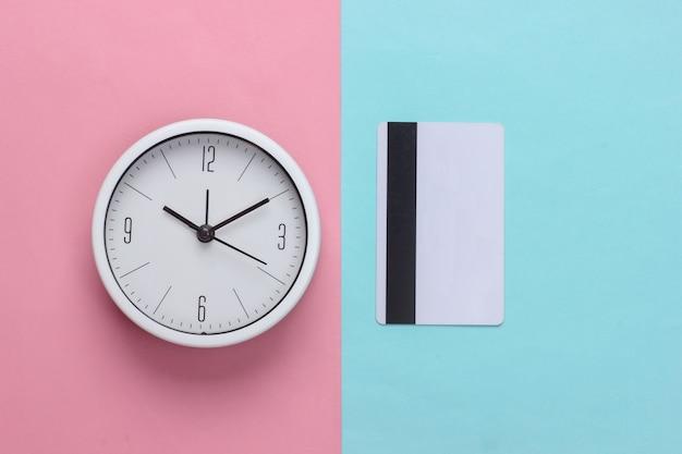 Weiße uhr mit einer kreditkarte auf einem blau-rosa pastellhintergrund. draufsicht