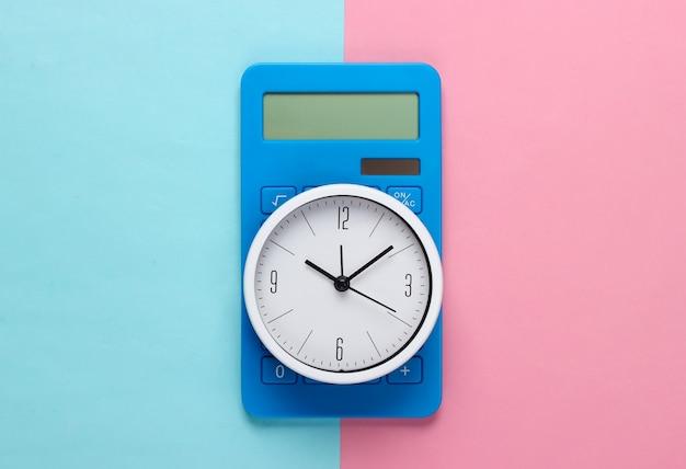 Weiße uhr und taschenrechner auf blauem rosa hintergrund. minimalistische studioaufnahme. draufsicht