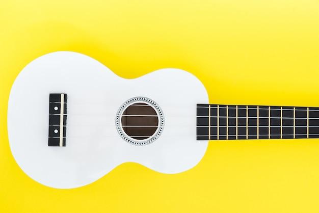 Weiße ukulele auf gelbem grund und mit einem platz für text. musikalisches konzept. flache lage