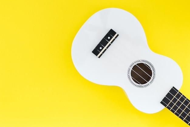 Weiße ukulele auf gelbem grund und mit einem platz für text. musikalisches konzept.