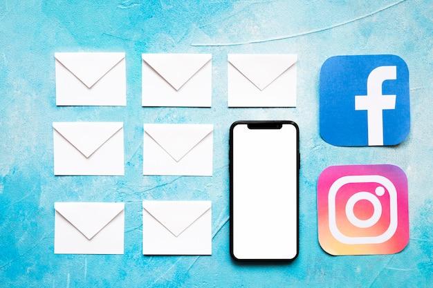 Weiße umschlagnachrichten des papiers und social media-ikone mit mobiltelefon auf blauem hintergrund