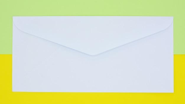 Weiße umschlagpost auf gelbem und grünem hintergrund