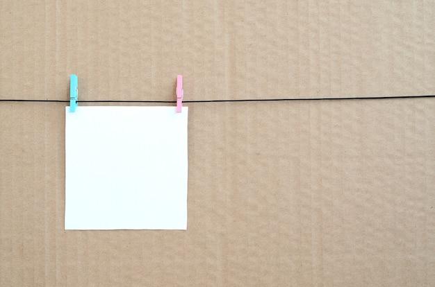 Weiße unbelegte karte auf seil auf einem braunen papphintergrund. kreative erinnerung, kleines blatt papier auf hölzerner wäscheklammer, notiz