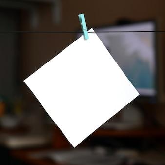 Weiße unbelegte karte auf seil, dunkler bürohintergrund. kreative erinnerung, kleines blatt papier auf hölzerner wäscheklammer, notiz