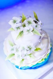 Weiße und blaue geburtstagstorte mit schönen blumen für mädchen und dekorationen für party