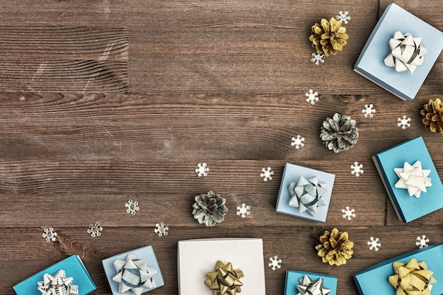 Weiße und blaue geschenkboxen, goldene und silberne zapfen und weiße dekorative schneeflocken.