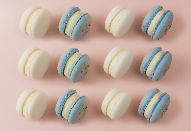 Weiße und blaue makronen auf dem tisch, makronen auf rosa oberfläche. hochwertiges foto
