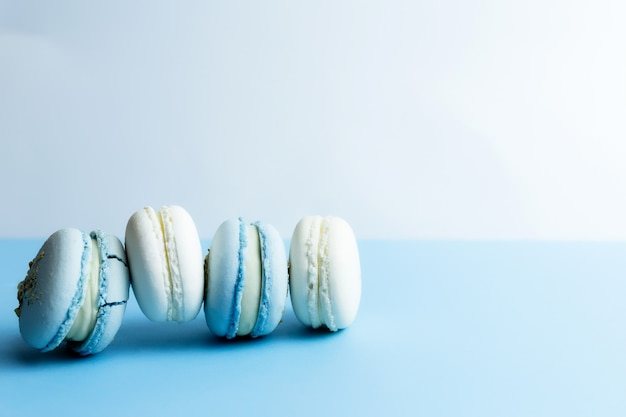 Weiße und blaue makronen auf dem tisch, makronen auf weißem blauem hintergrund.