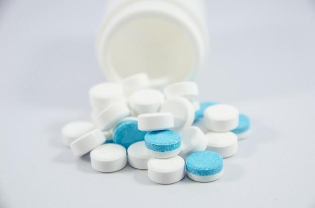 Weiße und blaue pille auf weißem blackground mit flasche