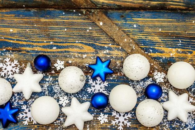 Weiße und blaue weihnachtskugeln und sterne, schneeflocken und vereinzeltes glitzern mit kunstschnee. vintage holzbretter in blautönen, draufsicht
