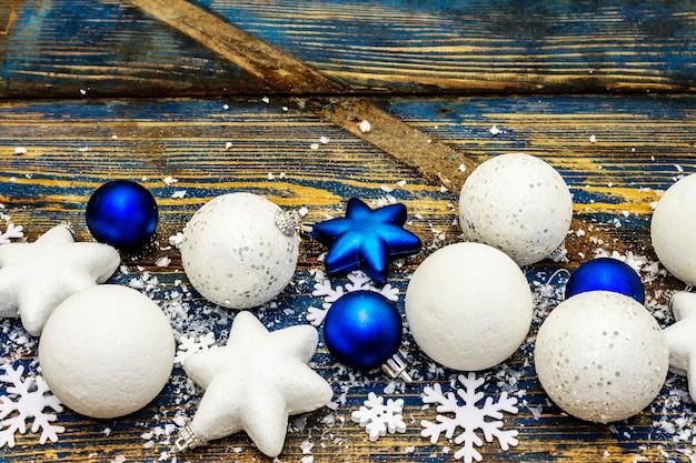 Weiße und blaue weihnachtskugeln und sterne, schneeflocken und vereinzeltes glitzern mit kunstschnee. vintage holzbretter in blautönen, kopierraum